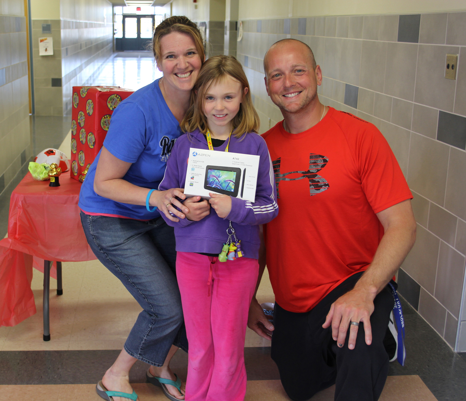 Third-grade student Ada Miller accepts a tablet presented by physical education  teachers Erin Waite and Phillip Thore. Provided photo