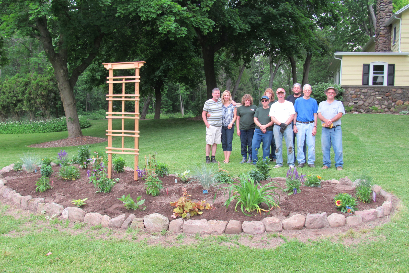 Orleans County Master Gardeners pose with homeowners Dan and Jill Ryan (far left) behind the newly installed perennial garden. K. Gabalski photo