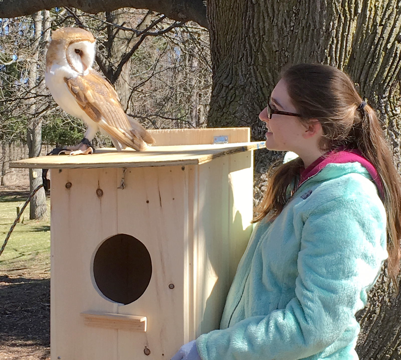 Leanne Walker, Girl Scout Ambassador of Troop 60779, holds one of the owl houses she made for her Gold Award while also making friends with a recent inhabitant. Provided photo