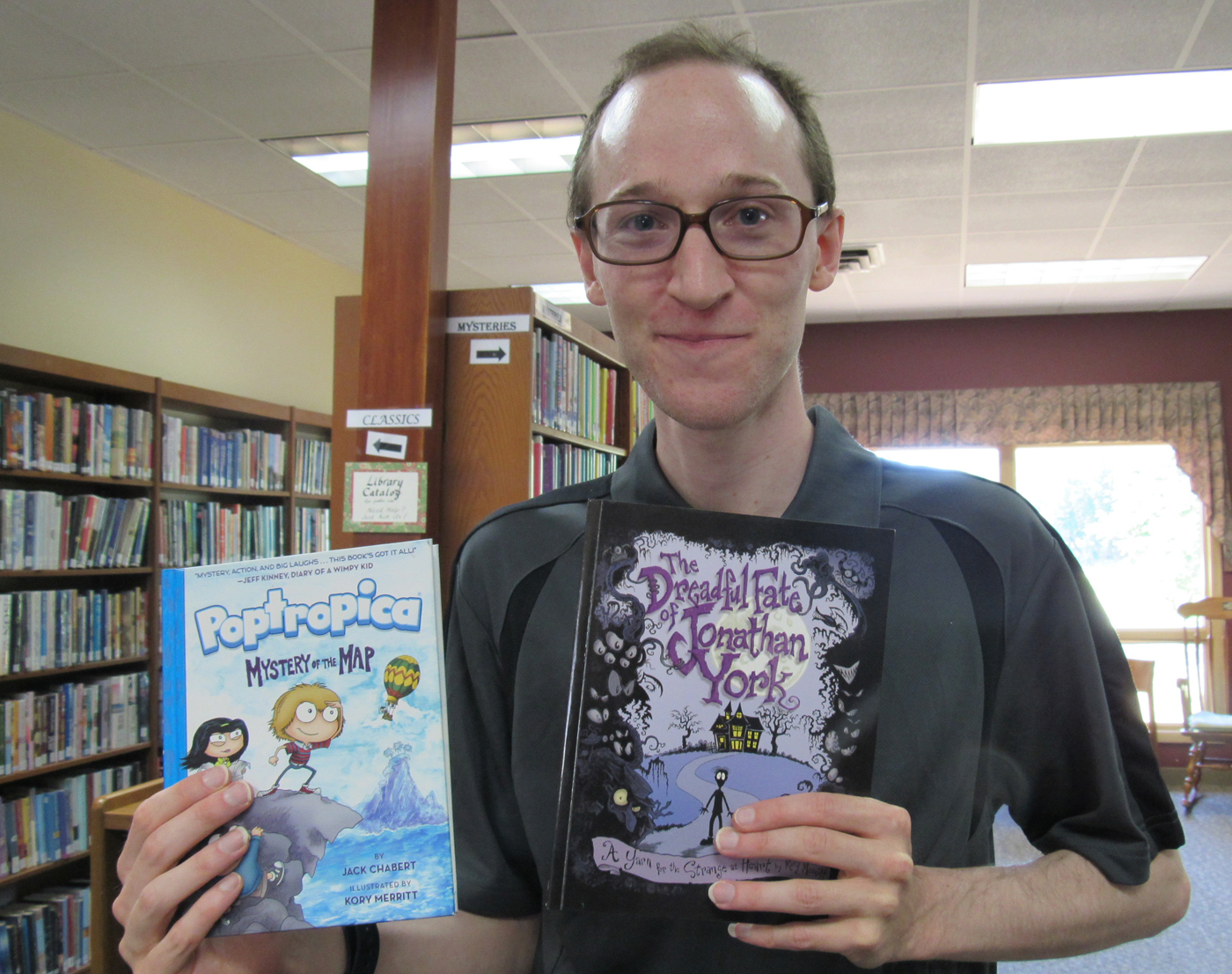 Kory Merritt of Spencerport poses with his two books:  Poptropica is part of a four book series created by Jeff Kinney and published in the spring of 2016; Jonathan York is written and illustrated by Kory and was published in the fall of 2015. K Gabalski photo