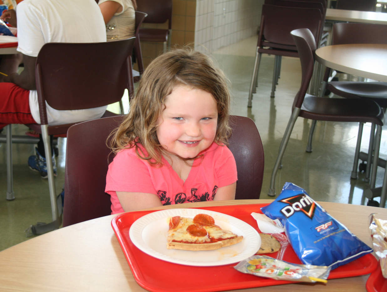 Lilly O'Brien enjoys her pizza lunch during the summer meal program. Provided photo