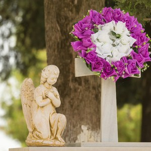 56545013 - flower garland and a statue on a grave after a funeral.