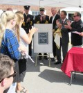 Congressman Chris Collins unveils the memorial plaque at the Post Office in Bergen Saturday, September 10.  It will now be the Barry G. Miller Post Office in honor of Miller who was killed a year ago in an accident involving ambulance in which he was riding to answer a call for help. Members of the Miller family are on the left. K. Gabalski photo
