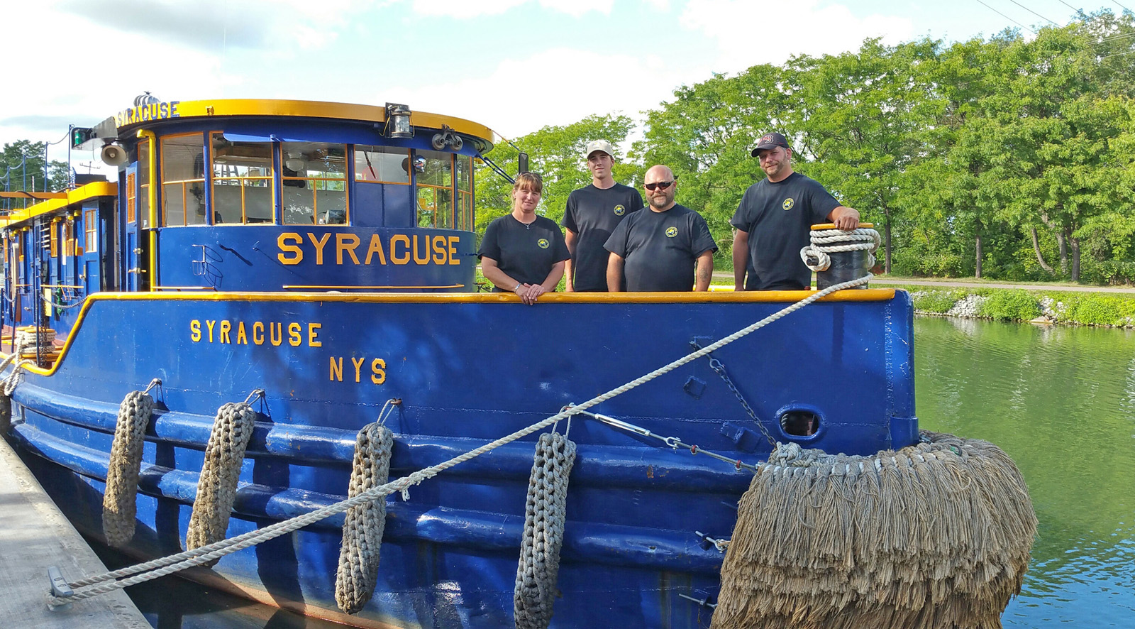 The crew of Tug Syracuse:  (l to r) Captain Wendy Marble, deck hand Seth Brant, marine engineer Jim O'Connor, and deck hand Jerry Spicer. They stay on the tugboat overnight. Photo by Dianne Hickerson