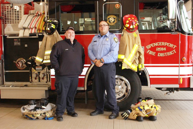 Spencerport Firemen Christian Geer and Richard Timothy Magin stand with their fire turnout gear in front of a Spencerport Fire Department firetruck. Photo by Maggie Fitzgibbon
