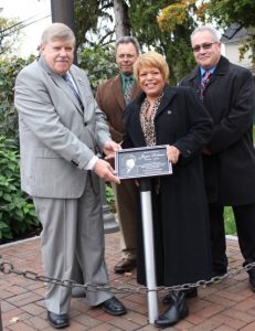 Gary Penders installs the Joyce Lobene plaque with the help of Mary, Jim and Mike Lobene. Photo by Maggie Fitzgibbon
