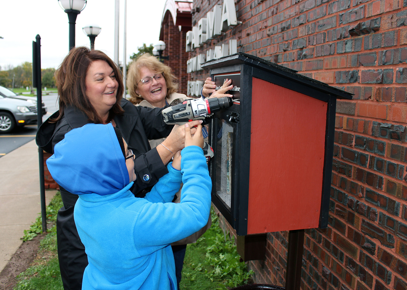 Aidan Harney, his mom Stephanie Harney (center), and Parma Town Clerk Donna Curry install a name plate on the new Little Free Library at Parma Town Hall. The library was made possible by Hilton Cares, an organization dedicated to projects that impact the health and well being of children in the Hilton School District. Provided photo