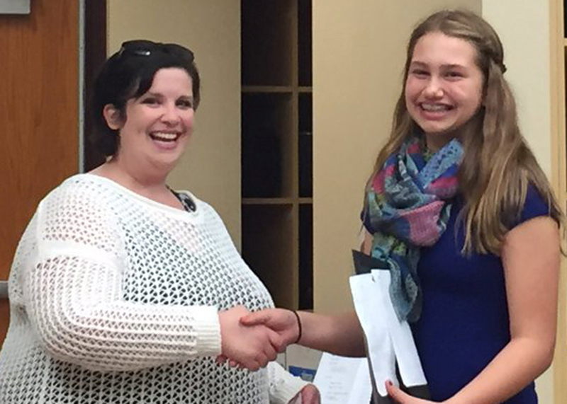 Byron-Bergen Music Boosters president Tara VanSkiver (l) accepts a donation for the school's music program from seventh-grader Madelynn Pimm (r). Provided photo