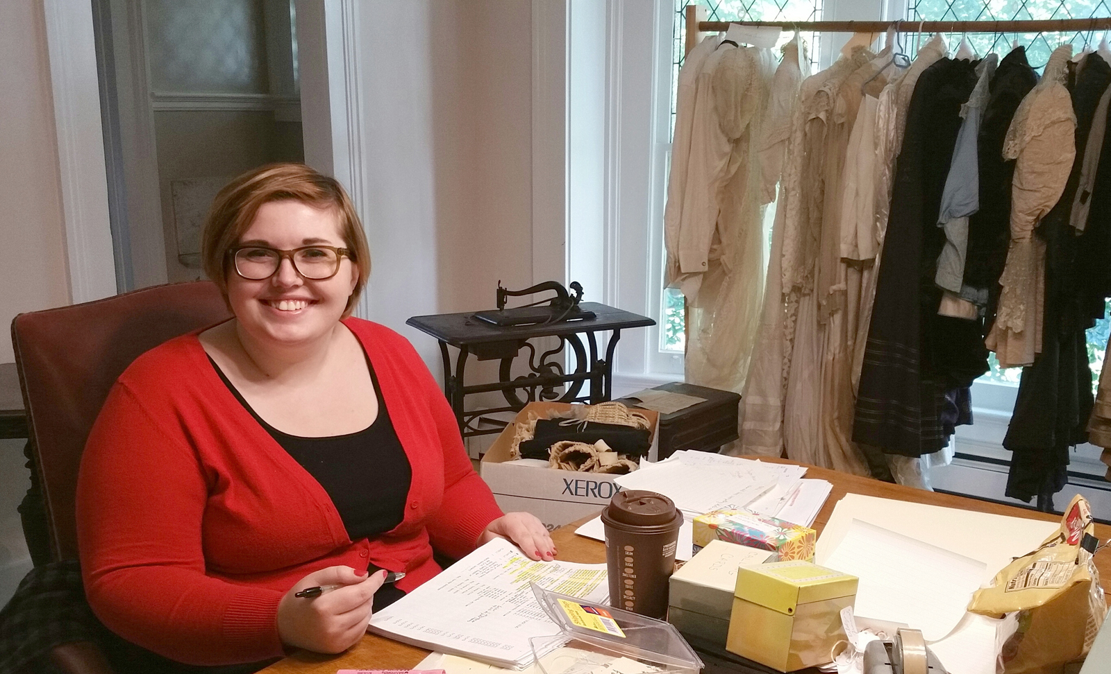 Alexandra Mills is at work with documents to sort and identify the WMHS clothing collection. In the background is a Grover & Baker sewing machine, circa 1863, which will be shown at the November 10 event. Photo by Dianne Hickerson