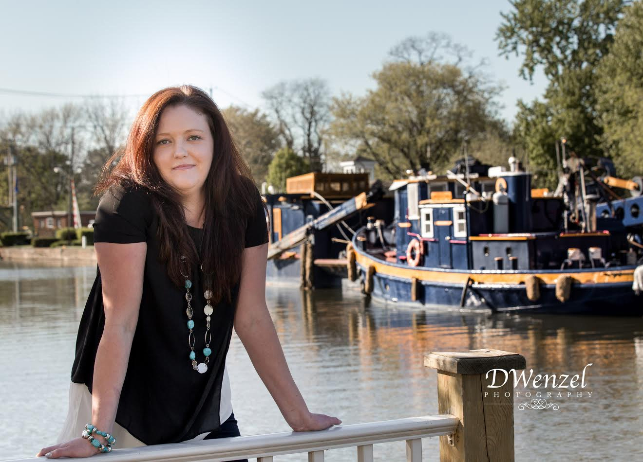 Nora Venezky stands outside the depot along the canal with a tugboat in the background. Provided photo