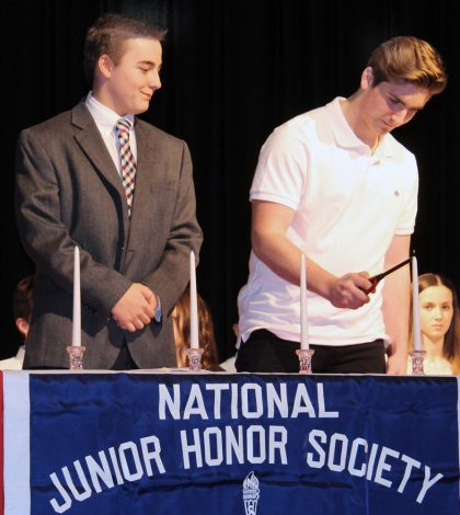 Merton Williams Middle School students Robert Chaffee (left) and Luke Danzig light candles representing the five characteristics of National Junior Honor Society membership.