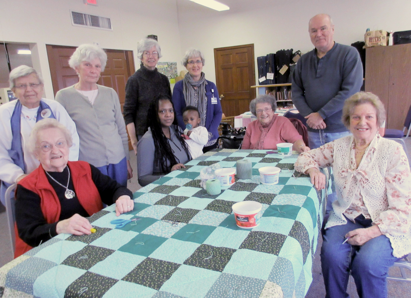 "Monday morning quilters and their ""tied,"" finished quilt (l-r): Front - Elsie Farmer, Sophia and daughter Lindsay Charles, Ruth Stahlecker and Phyllis Tornatello; back - Emma Wreader, Pat Cooper, Joan Smith, Terry Brown (guest) and Jim Smith."