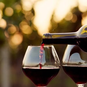 45249167 - pouring red wine into glasses in the vineyard, toned