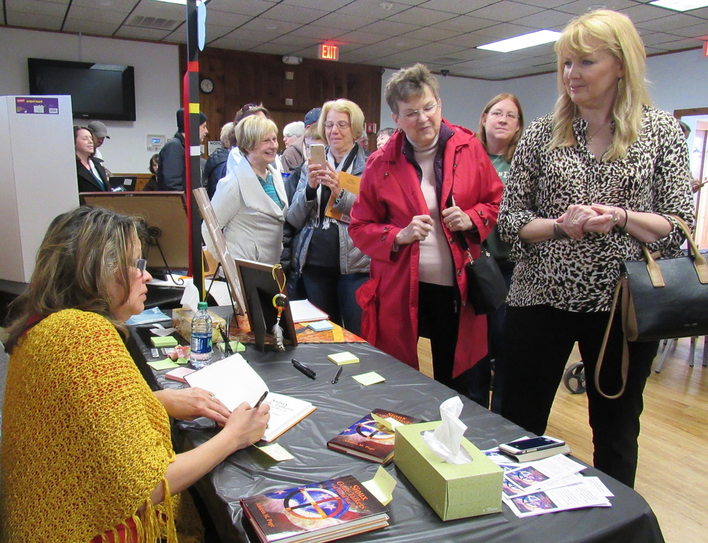 Local author/educator Andrea M. Page, seated at left, signs copies of her book, Sioux Code Talkers of World War II, during a book launch event held April 8 in Spencerport. K. Gabalski photo
