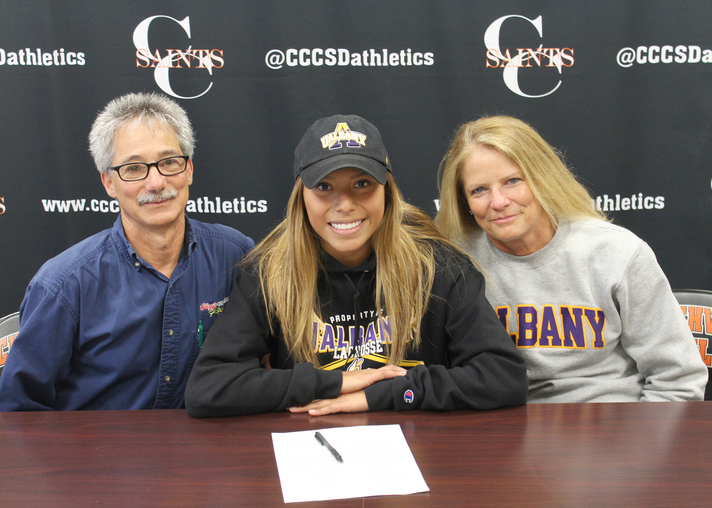 Saints lacrosse player Cheyenne Clark celebrates signing her National Letter of Intent to the University of Albany with parents Mike and Patricia. Provided photo