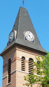 Two of the four clock faces on the Brockport United Methodist Church steeple seen from the corner of Main and State Streets in front of St. Luke's Episcopal Church.