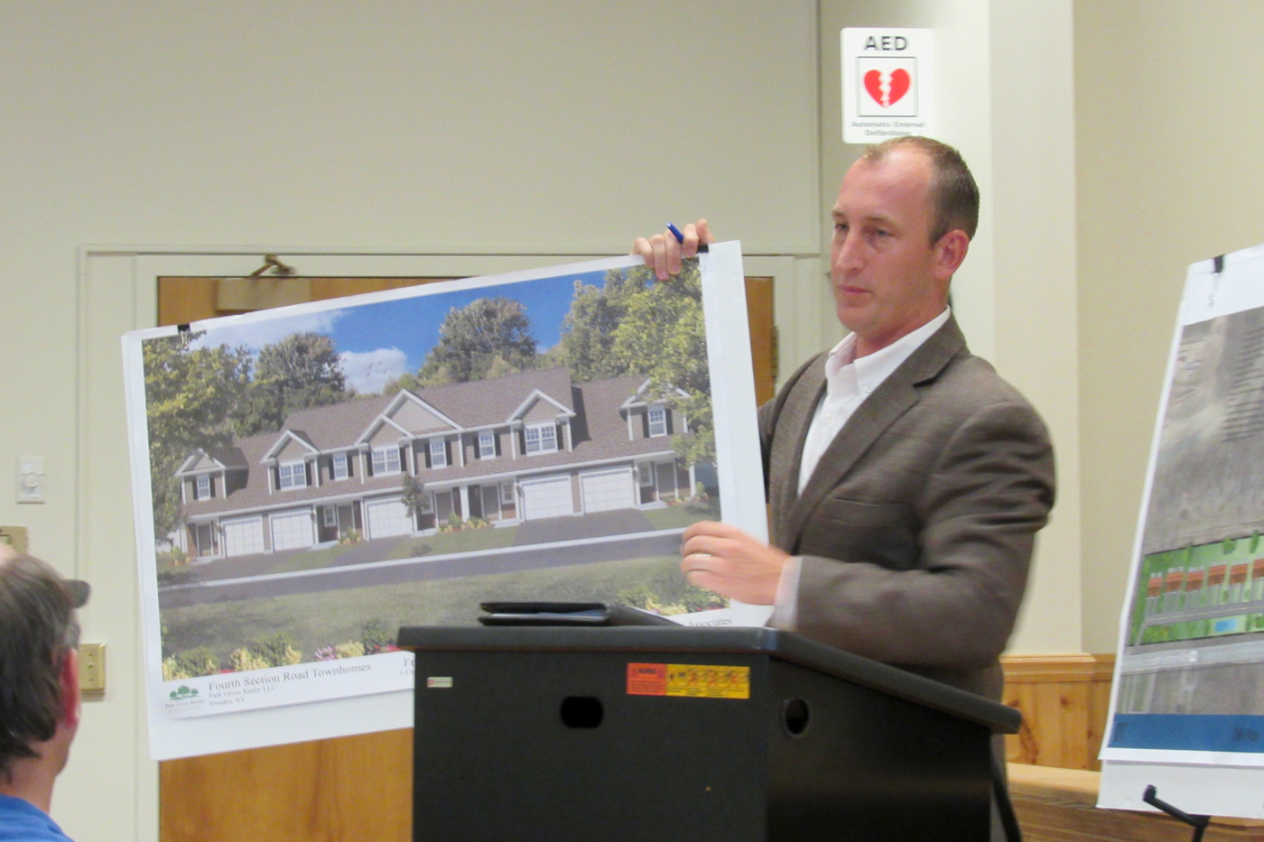 Jess Sudol, PE, of Passero Associates in Rochester, holds a concept elevation of what apartments proposed at the intersection of Fourth Section and Redman Roads in the Town of Sweden would look like.  Sudol spoke during a public hearing at the Sweden Town Hall July 25. K. Gabalski photo