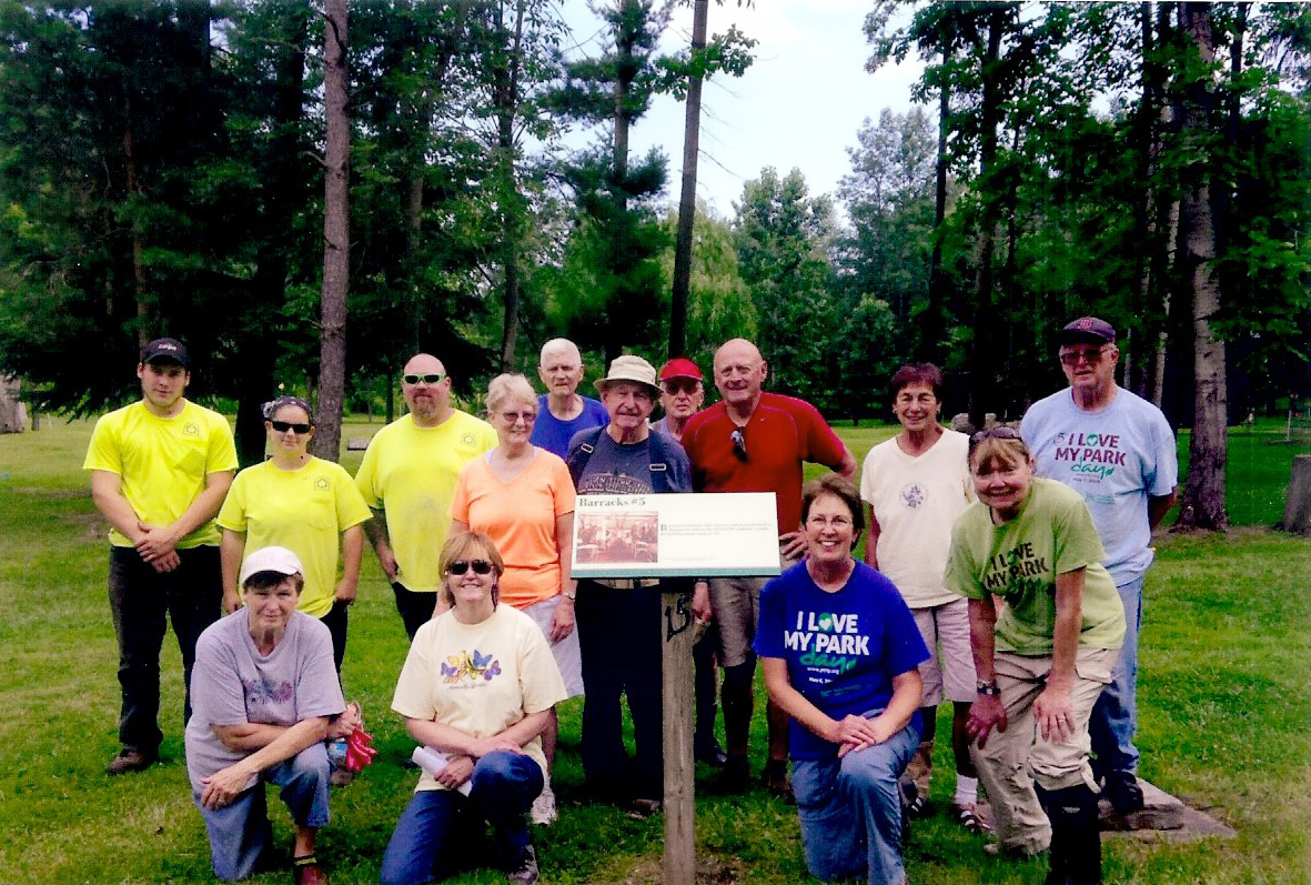 Members of the Friends of Hamlin Beach State Park and Hamlin Beach Park employees pose by one of the 30 signs they installed at the former CCC/POW site. Provided photo