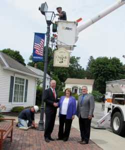 New York State Senator Mike Ranzenhofer (left) poses with Churchville Mayor Nancy Steedman and Monroe County Legislator Steve Brew on Wednesday, July 26, outside the Churchville Village offices. Linemen from Churchville Municipal Electric have been upgrading decorative lighting in the business district with LED fixtures thanks to a state grant secured by Senator Ranzenhofer. K. Gabalski photo