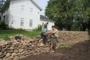Jean Colby and Donovan Berbeneciuc place additional stones on the wall at the historic Colby/Pulver House.  All stones were gathered from fields at Colby Farms and transported to the site. Colby says the rocks are a mix of different materials including granite, Medina sandstone and shale. Jean is standing on the steps which cut into the wall and lead to the house. K. Gabalski photo