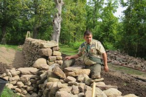 "Eagle Scout Donovan Berbeneciuc inspects the south end of the stone wall at the Colby/Pulver House. He says he received numerous ""granite kisses"" - pinched fingers and hands - during construction of the wall for his Eagle Scout project. K. Gabalski photo"