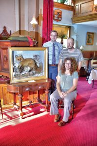 Matthew Ballard, Orleans County Historian (left); Bill Lattin, retired Orleans County Historian and retired director of Cobblestone Museum; and Melissa Ierlan, Clarendon Town Historian with the Akeley fox currently on display at Cobblestone Church. Photo by Rick Nicholson