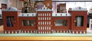 The Normal School Little Free Library as it appears on display at the Drake Memorial Library at the College at Brockport. It will eventually be mounted outside the Alumni House which is in front of Hartwell Hall on the campus. The model is 67 inches long, 22 inches high to the peak of the roof, and 12 inches deep. Photo by Dianne Hickerson