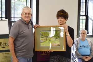 Ed Adams with Mayor Anna Marie Barclay presenting a painting he had done of Hartland Park to the Pavilion. Sage Pavilion is located in Hartland Park. Photo by Rick Nicholson
