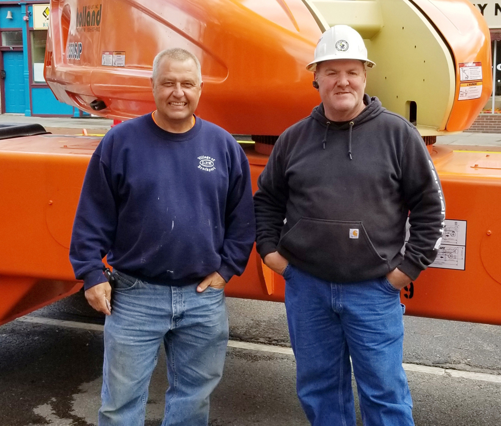 Dave Moore (left), foreman in the Village Department of Public Works stands with Greg Didas, owner of BBT Construction Services, Inc. They worked together to remove the last two clock hands while the main job was repairing the United Methodist Church roof. Photo by Dianne Hickerson