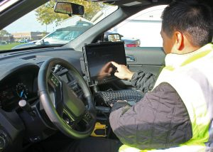 Security Officer Allain demonstrates the touchscreen and onboard capabilities of the new mobile digital computer. Provided photo