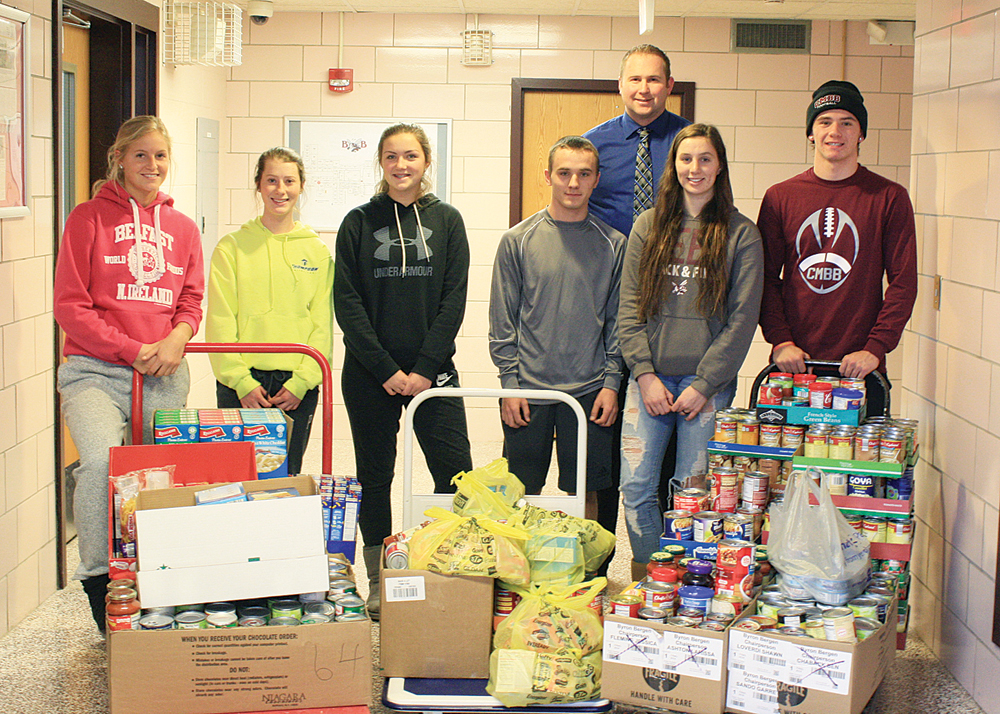 Varsity Club members with a few of the hundreds of donated items collected for the Holiday Food Drive. Provided photos