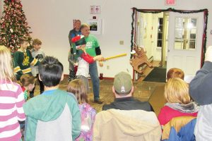 Paul Kimball assists a participant with the holiday pinata game. K. Gabalski photo