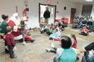 """Santa listens to Christmas wishes from young participants during the """"Umpteenth"""" Holiday Party in Clarkson. K. Gabalski photo"""
