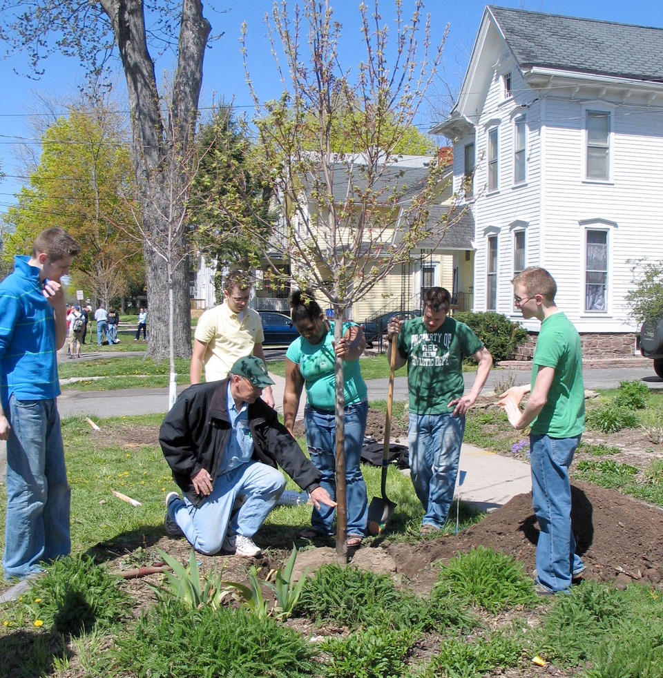 Rick Lair gives instructions to college students on the second annual Arbor Day, 2006, on Monroe Avenue. Background reveals other planting activity by more students. Lair was head of Facilities Maintenance at The College at Brockport (retired 2017) and continues as an ex-officio member of the Tree Board. Provided photo