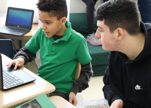 A second-grader at Fairbanks Road School shares his research and online presentation on artic mammals with a visiting high school student. Provided photo