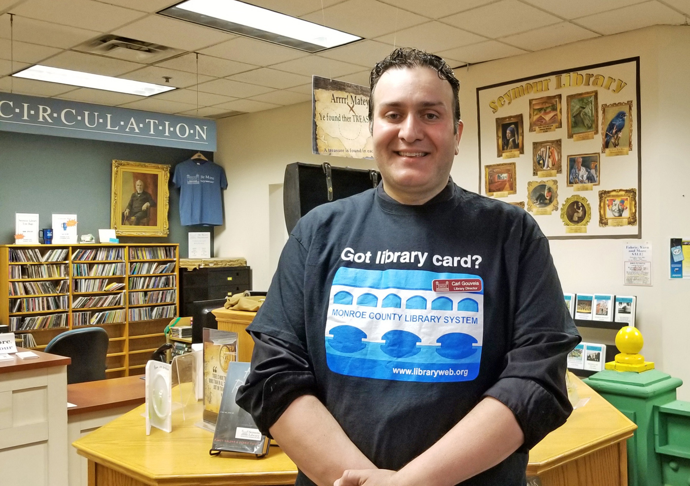Carl Gouveia is very much at home in Seymour Library where he is Director. His T-shirt message conveys his lifelong passion for libraries. Photo by Dianne Hickerson