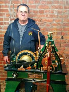 """Charles """"Chuck"""" Roeser stands with the clockworks which were restored by his company, the Essence of Time Tower and Street Clock Experts in Lockport. As hands-on owner of the company, he spent the day disassembling and assembling the unit that was carried up to the tower in parts. The clockworks were restored to the original condition including the pin stripe paint detail. Cables can be seen which are connected to weights that power the clock and bell strike. Provided photo"""