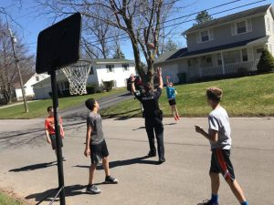 Officer Sims, while out on patrol, stops to interact and shoot hoops with Brockport youth. Provided photo