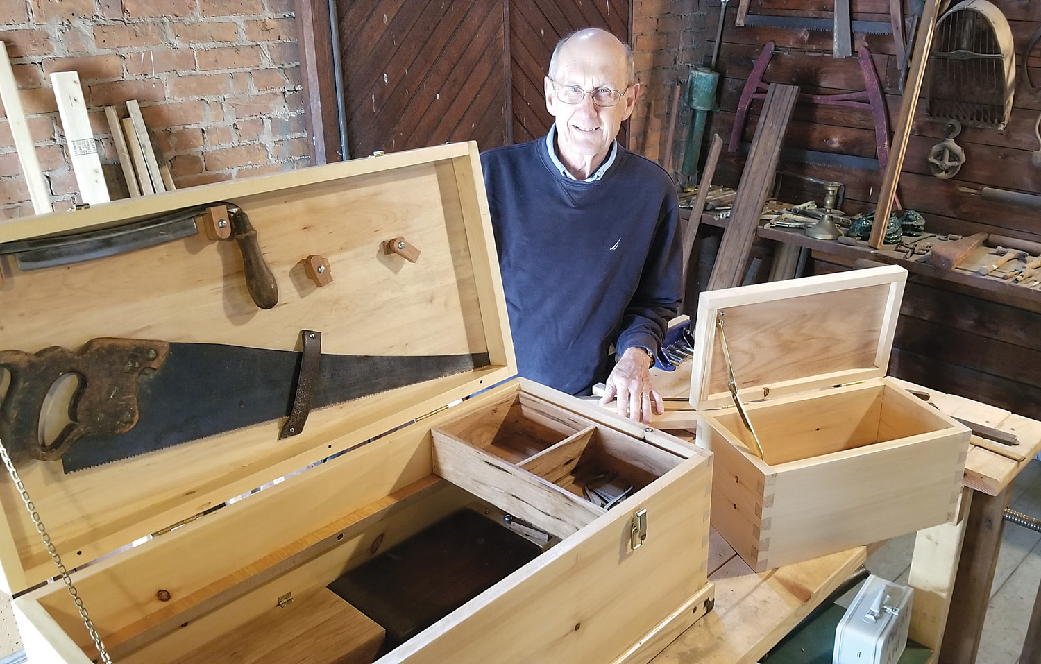 Gordy Fox stands with two model boxes that Carriage House Kids can build and take home in this summer's class on old-fashioned tools and carpentry. The shop is upstairs in the Carriage House on the Morgan-Manning House property. Photo by Dianne Hickerson