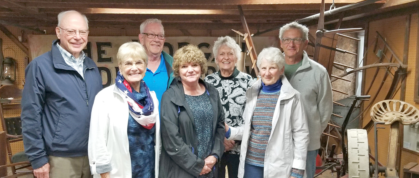 Assembled in the attic of the Emily L. Knapp Museum are (l to r) Topper Bott, Carol Bott, Bill Fitzgerald, Marcy Miceli, Sue Savard, Pat Kutz and Archie Kutz. Those standing with Savard are some of the 90 Welcome Center harbor masters who responded to the open house invitation. Photo by Dianne Hickerson