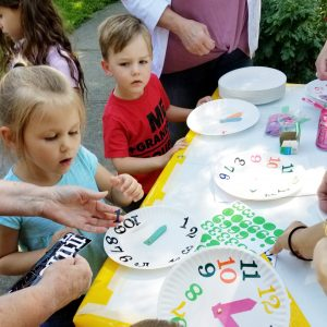 The MOMS club of Brockport helped children make their own clocks.