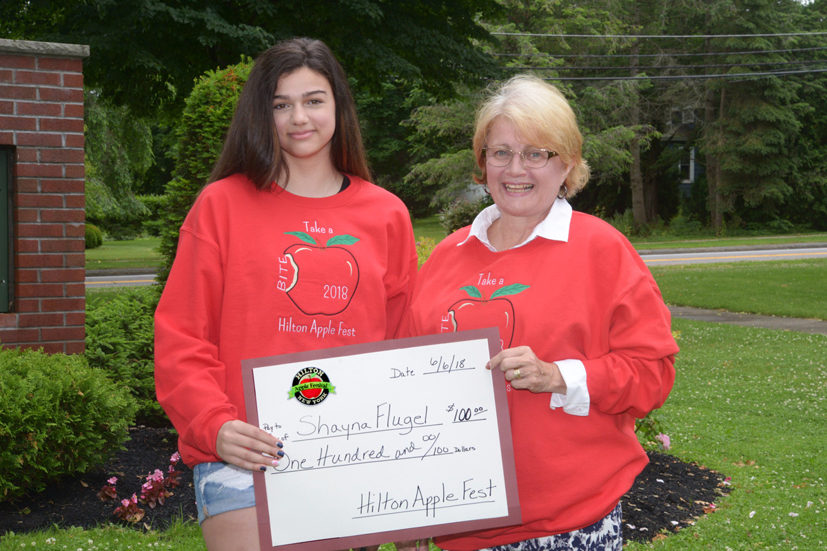 Shayna Flugel, winner of the 2018 Hilton Apple Fest Logo Contest, receiving her prize from Donna Curry, Logo Contest Chairman. Both are wearing sweatshirts bearing the 2018 Apple Fest Logo. Provided photo