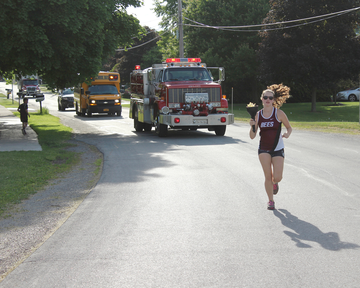 Runner Anna Hersom carries the Torch in Bergen as neighbors look on. Provided photo