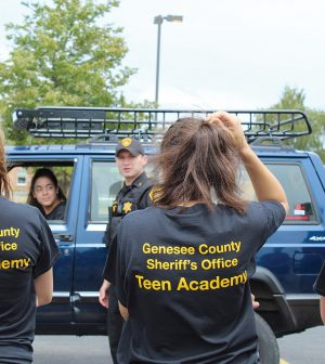 Genesee County Sheriff Deputy Andrew Mullen demonstrates traffic stop procedure with student participant Shaina DeJesus.  Photo by Gretchen Spittler.