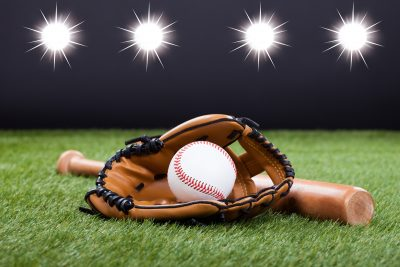 22059831 - baseball glove with baseball and bat lying on green grass