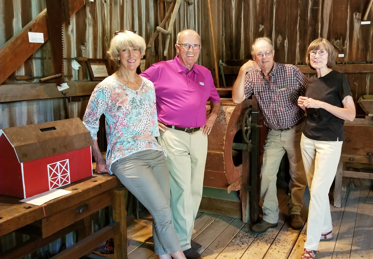 Posed amid antique farm equipment in the historic barn beind the Sweden Farmers Museum are (l to r): Brockport Village Mayor Margay Blackman, Allan Berry, Don Grentzinger and Kathy Goetz. Berry is president of the Brockport Community Museum (BCM). Grentzinger is on the Town of Sweden Museum board. Kathy Goetz is Town of Sweden Historian, a member of the BCM board and of the Sweden Farmers Museum board. She also heads the Farmer Museum's Barn Committee. Missing from the photo are: Kevin G. Johnson, Town of Sweden Supervisor. Chris Hunt, chairperson of Sweden Farmers Museum board. Shown is a model of the barn made by Grentzinger. Photo by Dianne Hickerson