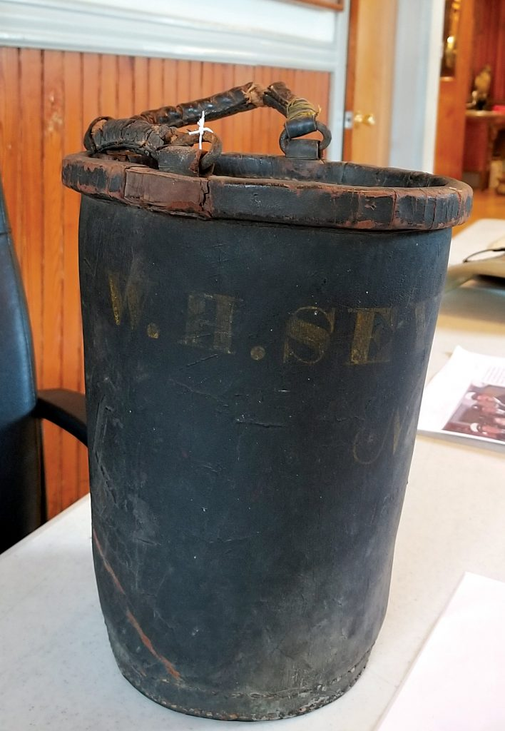 """The leather bucket, cc. 1840, has """"#4 W.H. Seymour"""" imprinted. The Village required a fire bucket at each residence to help when the fire alarm sounded. This is the bucket from William Seymour's own residence. Each family had their own name printed on the bucket."""