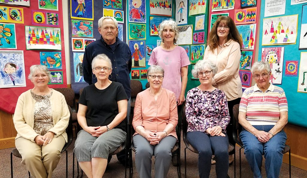 """Attending the May 21 Friends of Seymour Library meeting were (l to r) - seated: Charlotte Wright, Debbie Cody, Carolyn Mundy, Linda Sanford, and Mary Marone. Standing: Dan Burns, Lynne Gardner and Karen Sweeting. The photo was taken in the Seymour Library Duryea Room against a background of art work by Mrs. Della Buzard's art students at the Cornerstone Christian Academy in Brockport. Art work from the community is often displayed here, contributing to the library's unofficial identity as a """"community center."""" Photo by Dianne Hickerson"""