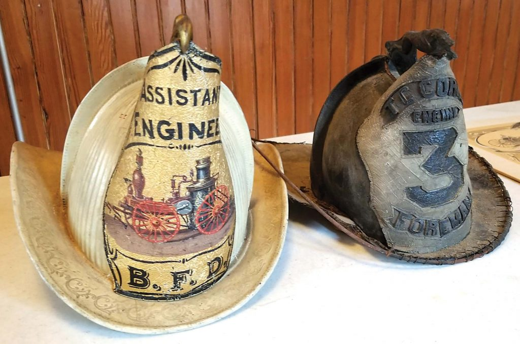 """The older helmet (right) reads """"T.C. Corn, Engine #3, foreman."""" It goes back to the Thomas Corn Engine and Hose Co. that operated the hand pumper. Thomas Corn was a prominent citizen and one of the early presidents of the village. """"Foreman"""" was another word for """"Captain."""" The newer helmet (left) was worn by the assistant fire chief called an """"Assistant Engineer"""" (word at top) in the late 1800s or early 1900s. Photos by Dianne Hickerson"""