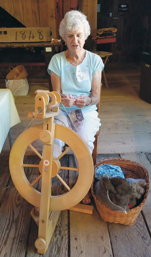 Marion Dilger used her antique spinning wheel to demonstrate how fibers are spun into yarn.